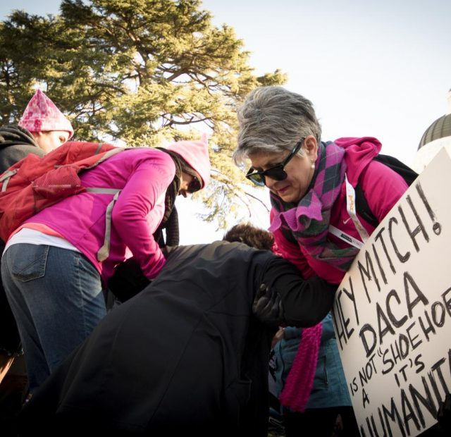 Angelica Orozco helps lift women over a cement barrier that leads to the Capitol where the annual Women's March demostrations are taking place on Jan. 20, 2018 in Sacramento, California.