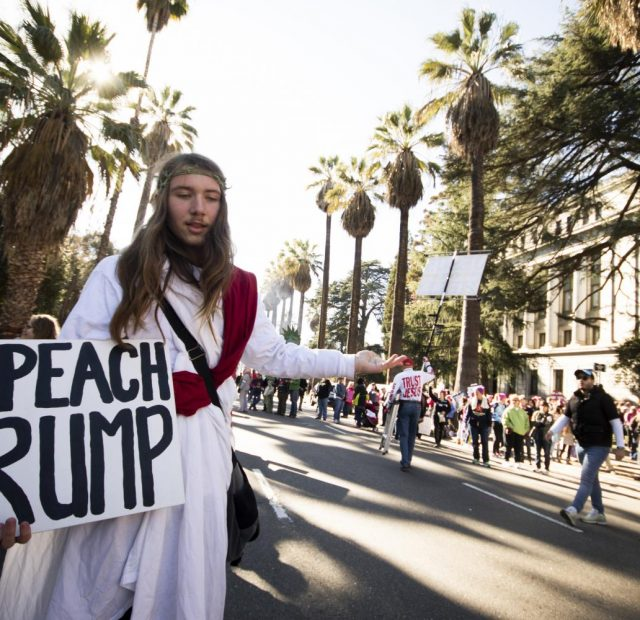 """Jesus Christ"" poses with his protest sign in front of the California State Capitol during the 2018 Women's March on Jan. 20, 2018."