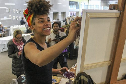 Artist Aliyah Sidqe stood above a crowd of onlookers as she spent two hours painting live during American River College's Black Heritage Celebration on Feb. 22.  (Photo by Jennah Booth)