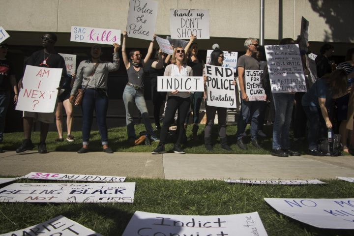 Protest signs lay on the ground as demonstrators chant in front of the Sacramento County District Attorney's office on March 29, 2018. (photo by Ashley Hayes-Stone)