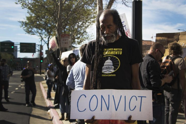 A demonstrator stands with his sign in front of the Robert T. Matsui United States Courthouse during the protest of Stephon Clark's death on March 29, 2018.