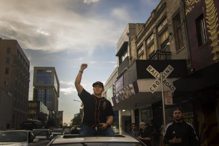 A civilian raises his fist as he sits on top of his car while the demonstrators block the intersections of downtown Sacramento on March 29, 2018.