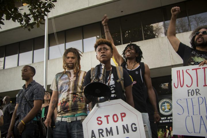 Demonstrators protest in front of the Sacramento County District Attorney's office on March 29, 2018.