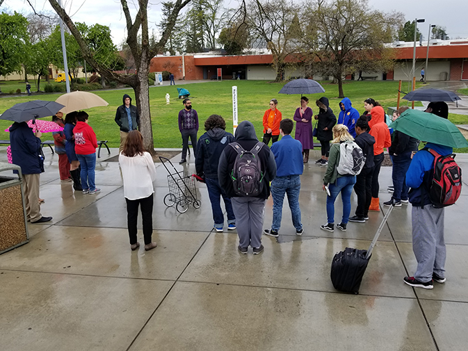 American River College students and faculty gather around a makeshift vigil in front of the library on March 14. They walked out of class and held 17 minutes of silenece in honor of the Parkland High School shooting victims. (photo by Mack Ervin III)