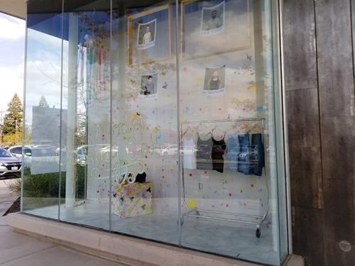 Clothes and photos hang in a display outside of the Science and Fine Arts Building for the Fashion Show Model Casting on March 16. (Photo by Hannah Yates)