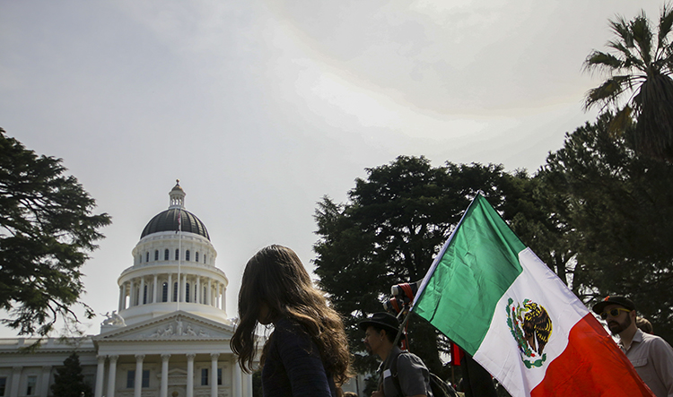 Protesters+carry+a+Mexican+flag+outside+of+the+California+State+Capitol+on+March+31%2C+2018.