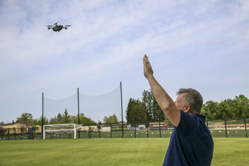 Shane Lipscomb lifts his hand to the sky in an effort to lock in to the drones smart capture, where the drone will follow hand signals, to get it to land without a remote. April 4, 2018. (Photo by Brienna Edwards)