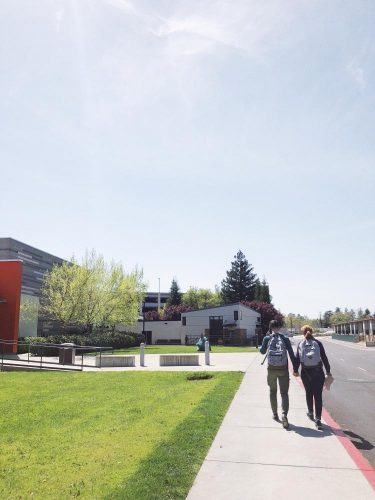Students hold hands as they walk around campus at American River College on April 20, 2018. (photo by Alondra Botello)