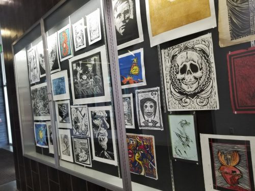 The students' artwork hangs on the wall in the Life Science and Fine Art building at American River College on April 9. (photo by Hannah Yates)