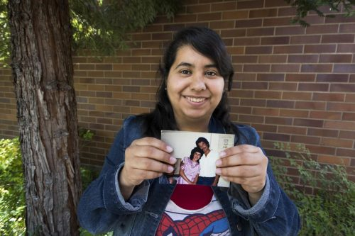 Staff writer Cecilia Castillo Juarez holds a 1988-era photo of her parents in their home of Mexico. (photo by Ashley Hayes-Stone)
