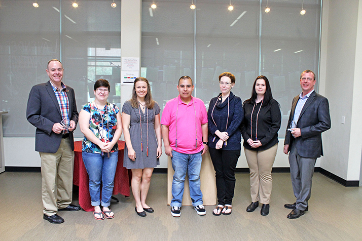The Lavender Graduation graduates (from second-left to right: Wendy Campbell, Madalyn Parker, Sergio Salcedo-Contreras, Kelley York, Heather Ogden) pose with their rainbow tassels, standing side-by-side with the Pride Award winners (left: Brett Spencer right: Dennis Lee, Jenna Grossman not pictured) at the Hub, May 4. (Photo by Hannah Yates)