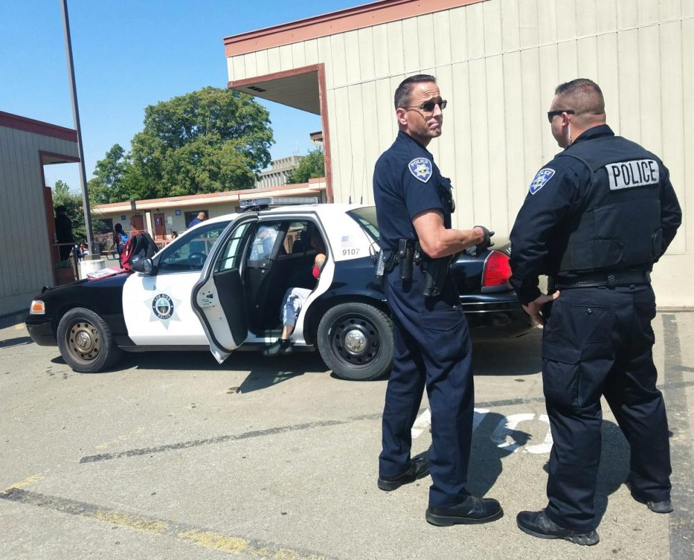 Los Rios Community College officer Joe Quirarte and a fellow officer detain two suspects of a potential altercation at American River College on Aug. 27, 2019. (File Photo)