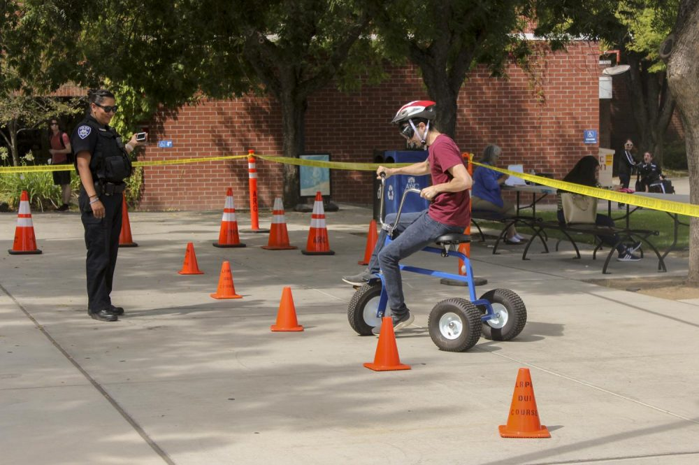Allen+Marinovich%2C+Chemistry+major%2C+tries+to+make+a+turn+with+a+tricycle+while+wearing+alcohol+impairment+simulation+goggles.+Officer+Rosie+Salazar+from+Los+Rios+Police+department+makes+sure+students+are+safe+during+the+simulation.+%28Photo+by+Itzin+Alpizar%29+