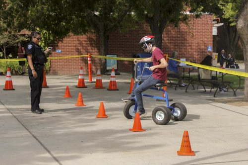 Allen Marinovich, Chemistry major, tries to make a turn with a tricycle while wearing alcohol impairment simulation goggles. Officer Rosie Salazar from Los Rios Police department makes sure students are safe during the simulation. (Photo by Itzin Alpizar)