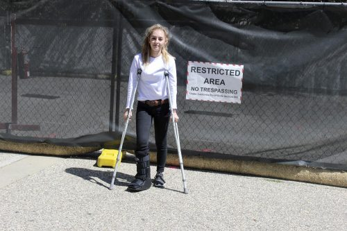 Taylor Ryan, a student at American River College whose major is undecided, stands holding crutches in front of the fencing around the construction on Sept. 13, 2018. Navigating around the site has been challenging for students with disabilities and other accommodations. (Photo by Hameed Zargry)