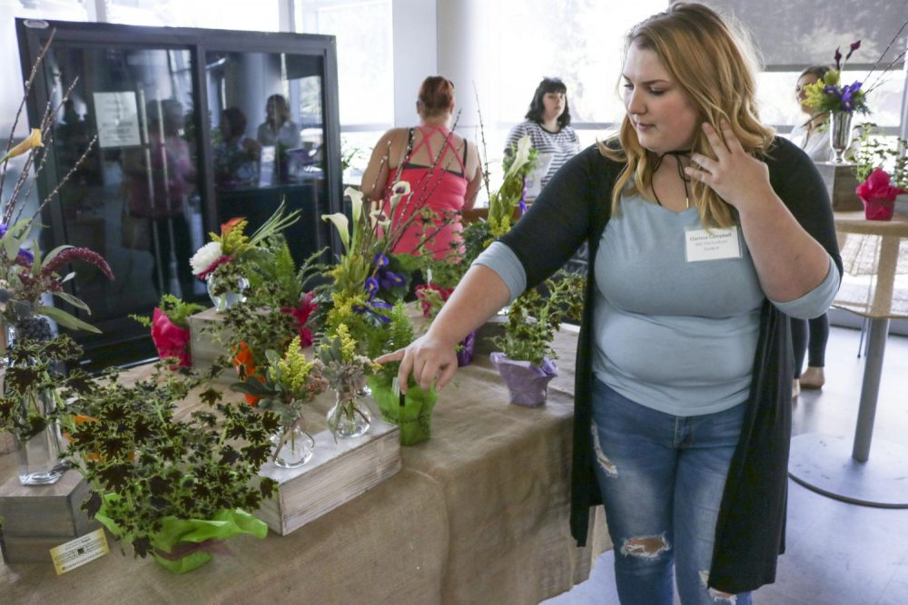 Horticulture major Clarissa Campbell shows the different flowers arrangements during the Flower Sale in the Student Center at American River College on Sept. 20, 2018. (Photo by Imani Smith)