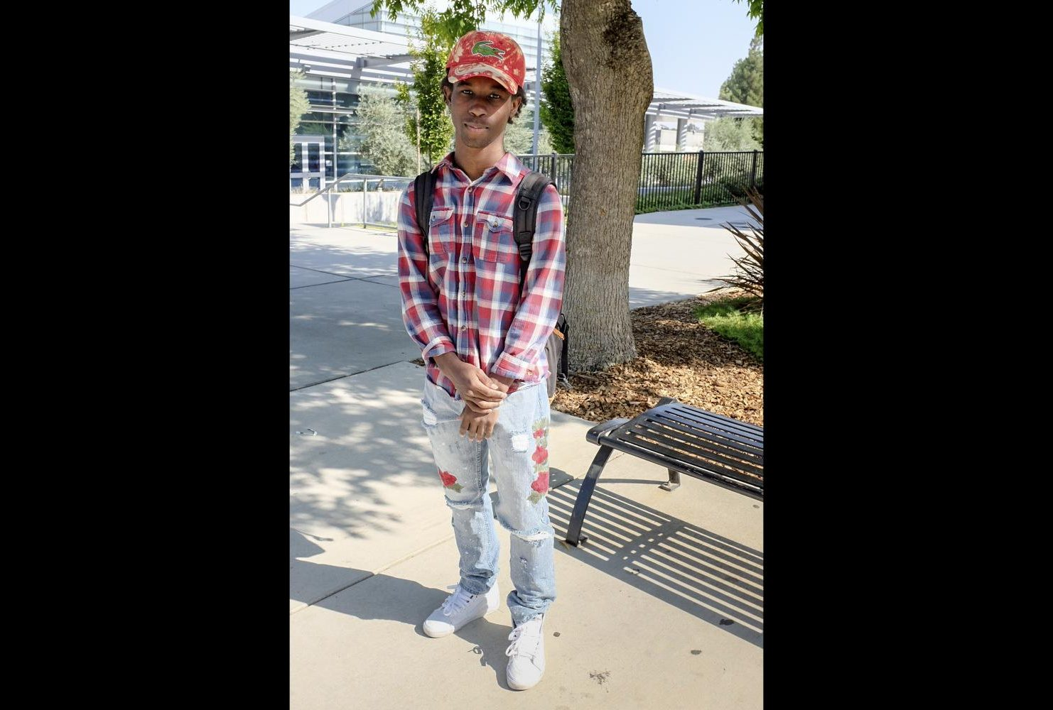 "Computer Engineering major, Devontae Robinson wears a checkered flannel shirt in American River College colors and jeans with embroidered roses on each leg at ARC on Sept. 4. ""You don't have to wear designer to be stylish. People wear $4,300 Gucci shoes or $1,000 shirts and that's so called style,"" Robinson said. (Photo by Patrick Hyun Wilson)"