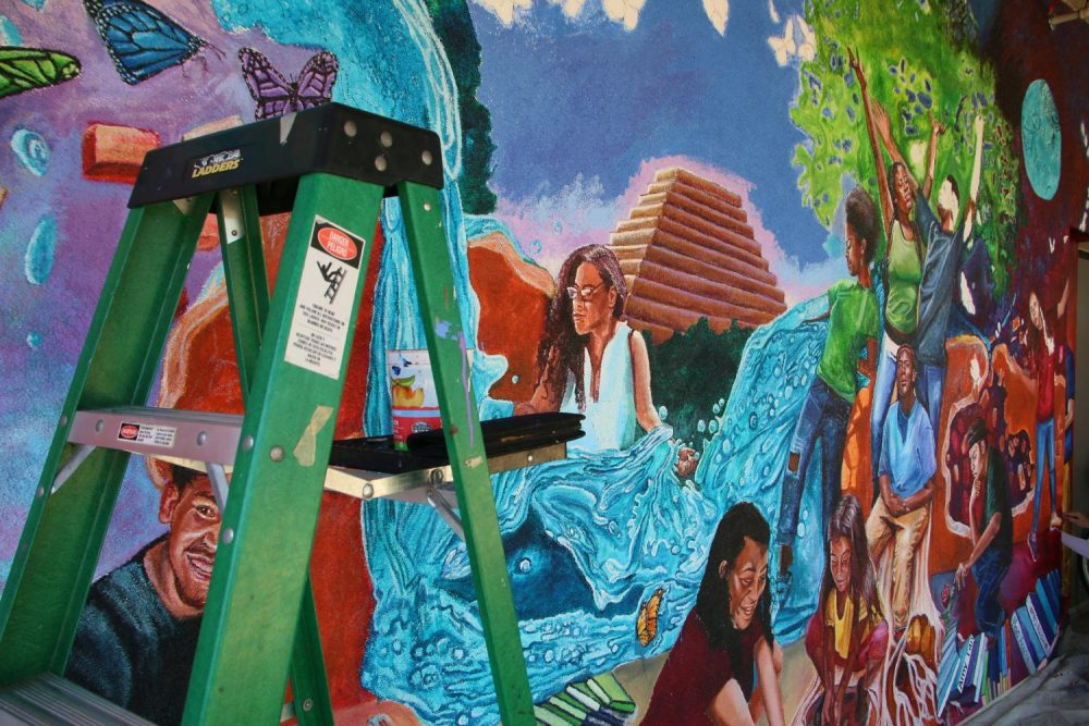 A mural being painted outside of the Learning Resource Center features the likeness of students and symbols that represent Sacramento and American River College on Sept. 1 2018. (Photo by Jennah Booth)