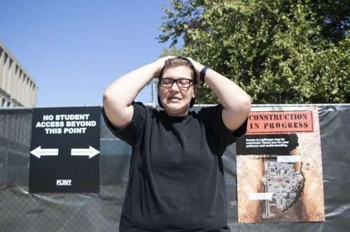 Opinion editor Tracy Holmes poses in front of the gated-off Liberal Arts building during construction at American River College on Sept. 10, 2018. (Photo Illustration by Ashley Hayes-Stone)