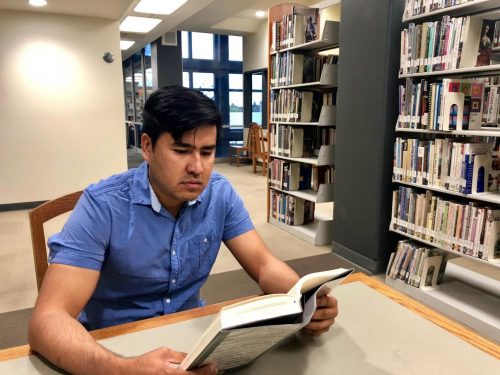 Mohammad Ewaz Wafai, political science major and former interpreter for the U.S. Army reads in the library at American River College on Oct. 3, 2018. (Photo by Hameed Zargry)
