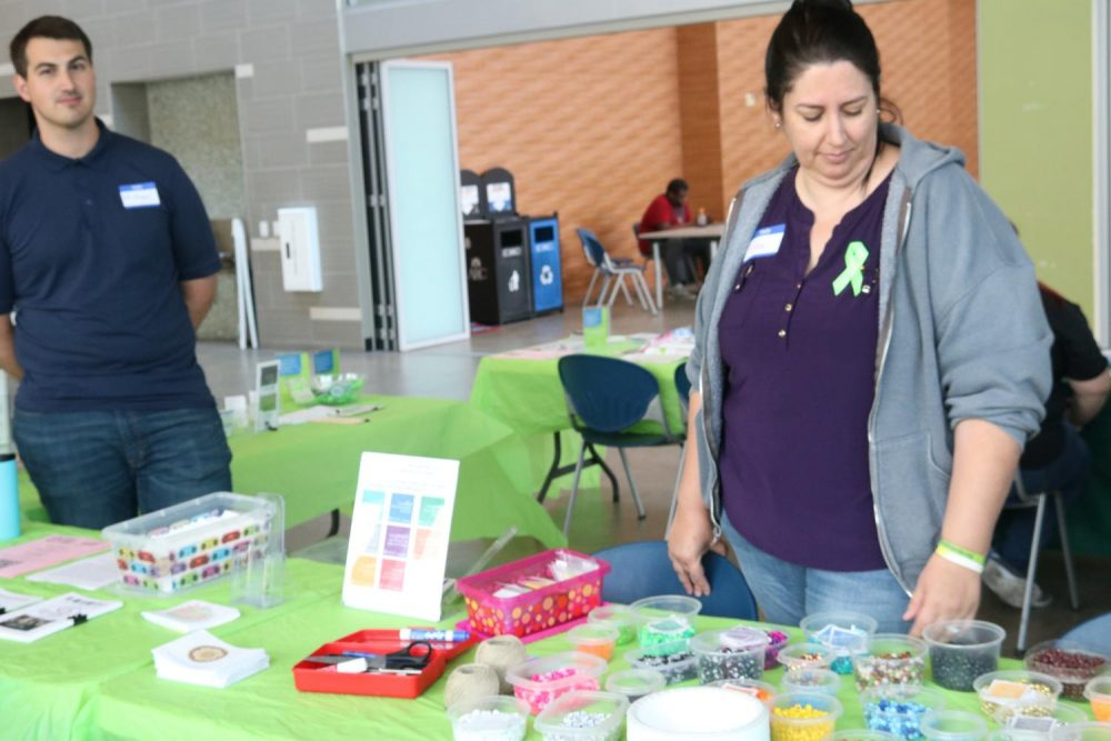 Tina Hardwin, the Club and Events Board representative for NAMI on Campus, looks at beads that represent the loss of a loved one while hosting a table for Welcome Day in the Student Center at American River College on Sept. 13, 2018.