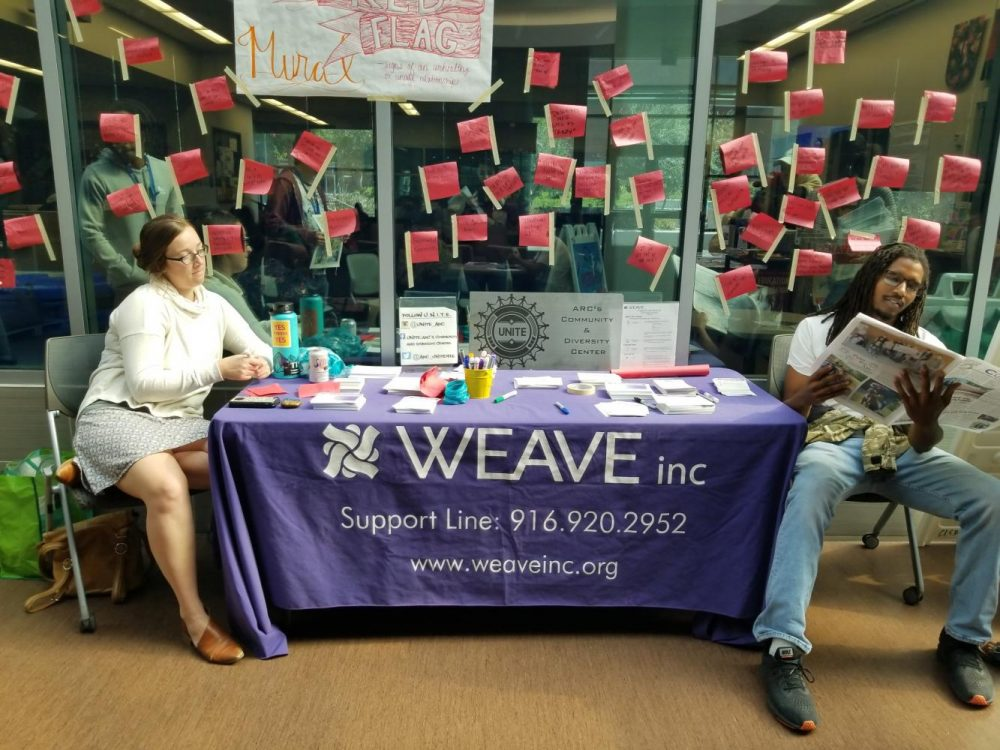 Elissa Crandall, the Los Rios Community College District WEAVE confidential advocate, adds to a display of dating 'red flags,' as kinesiology major Haven Bishop reads an issue of the Current at a WEAVE display in front of the Hub in the Student Center on Oct. 17, 2018. (Photo by Hannah Yates)