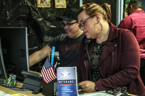 Nicole Williams (right) the Trio Veterans Program advisor answers the phone while computer science major Spencer Barns works on the computer in the Veterans Resource Center on Oct. 24, 2018 at American River College. (Photo by Tracy Holmes)