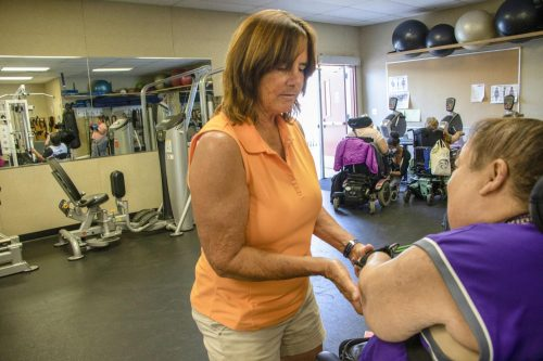 Professor Raye Maero assists computer science major Allison Murdaugh with seated row exercises during an adapted weight class in the at American River College  on Oct. 8, 2018. (Photo by Christian Sutton)