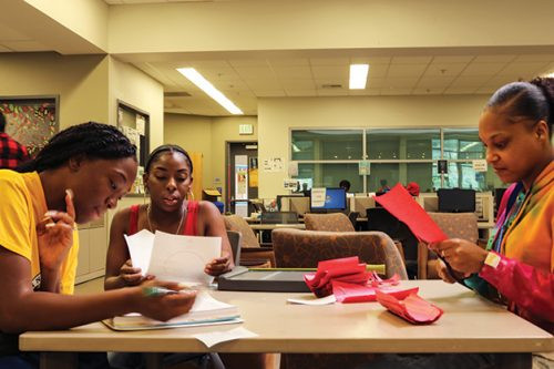 Umoja Sakhu club members Raqhale Brooks, (left) pre-law major, Nyla Aaron, (center) undecided major and Grace Swint, (right) political science and sociology major study in the Hub Center at American River College on Oct 15, 2018. (Photo by Breawna Maynard)