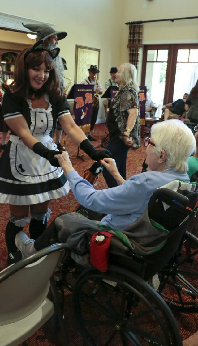 """Xylina Catipon, psychology major and president of Psi Beta club helps a resident of the Oakmont of Carmichael to dance on their wheelchair. The student volunteers from Psi Beta chapter from the American River College volunteered on October 20 helping the residents to enjoy the Oktoberfest event with music by the band """"Your musical memories"""" that focus on music from the 20s, 30s and 40s."""