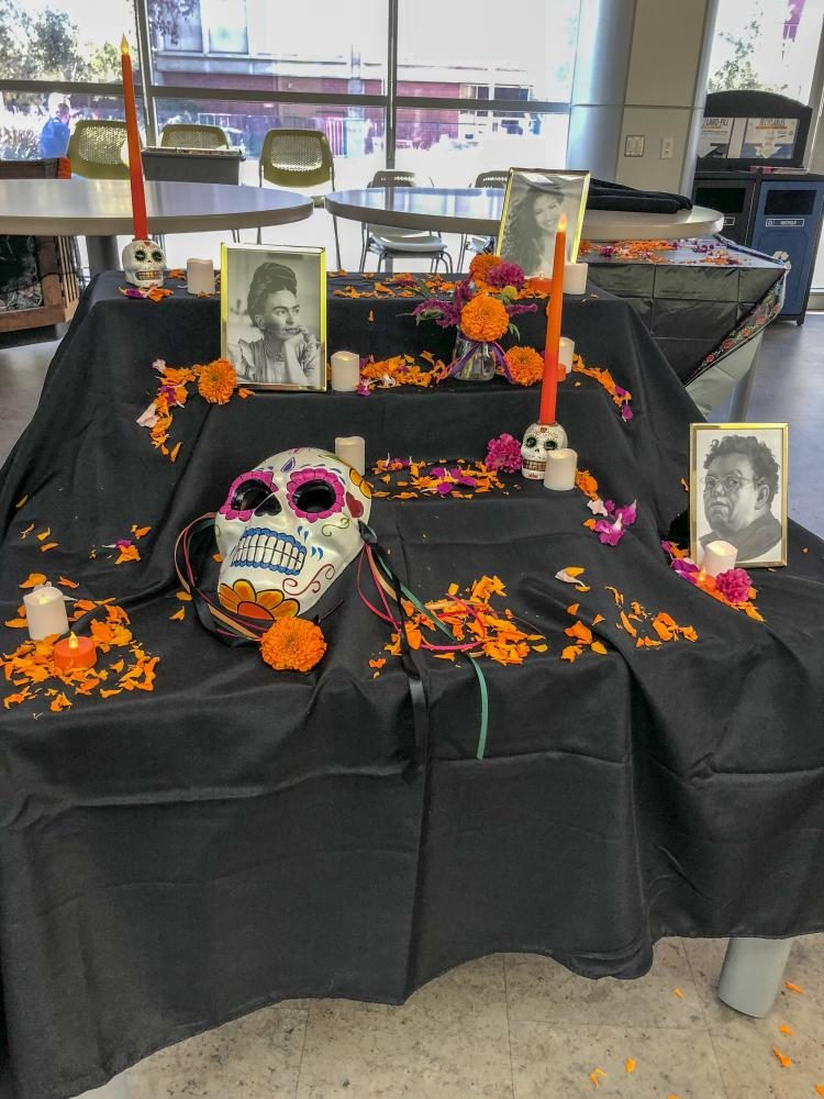 The horticulture department's flower sale incorporates an alter that displays photos of significant Latino figures during a Day of the Dead celebration in the Student Center at American River College on Nov. 1, 2018. (Photo by Alexus Hurtado)