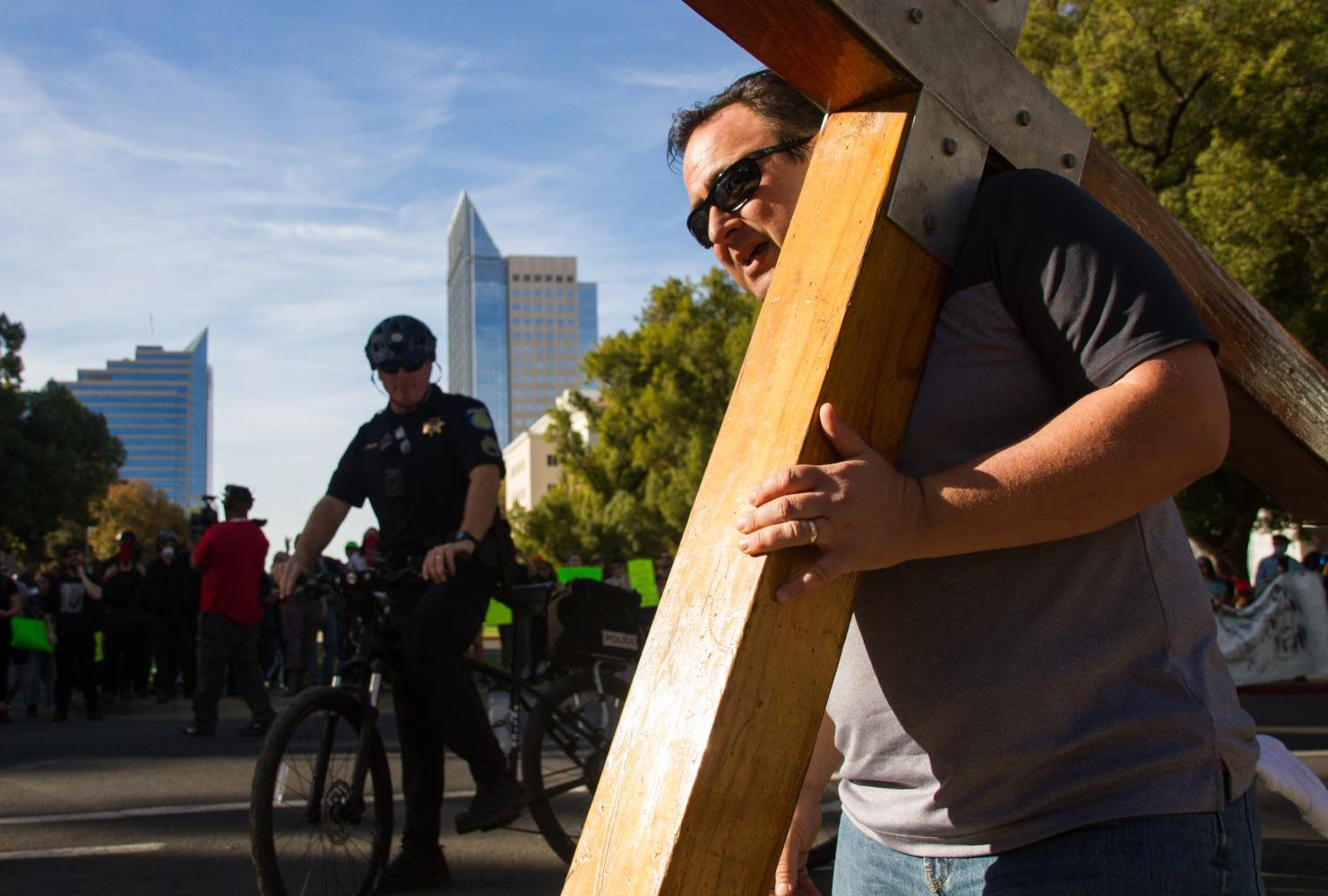 "A demonstrator at the ""Turn California Red"" conservative rally carrying a wooden cross onto the sidewalk at the California State Capitol in Sacramento on Nov. 4, 2018. (Photo by Patrick Hyun Wilson)"