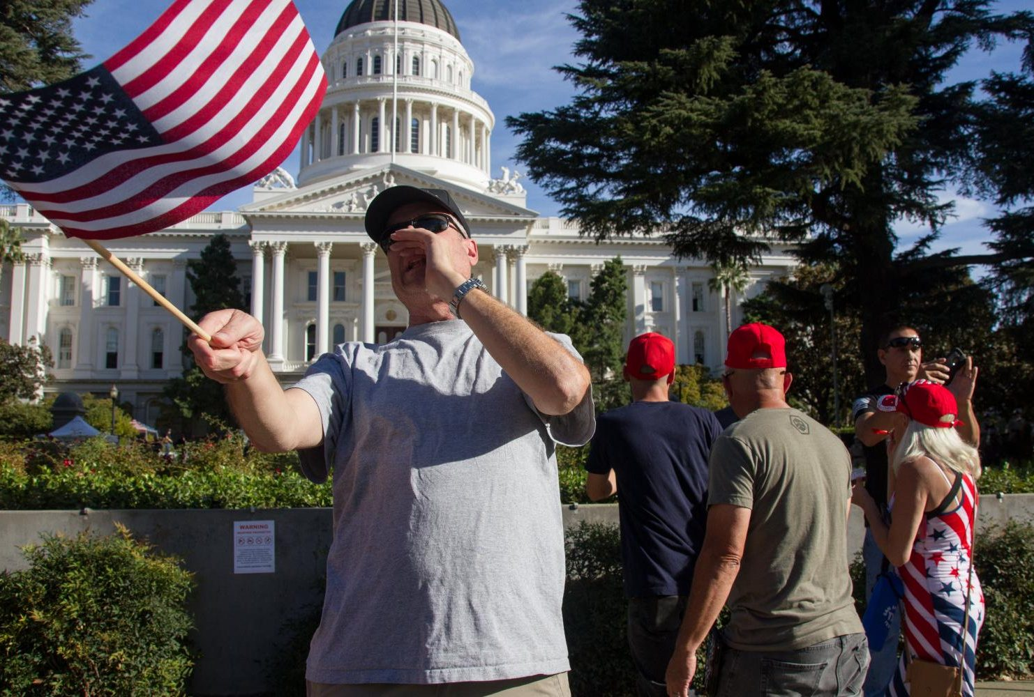 "A demonstrator waving an American flag at the California State Capitol during a ""Turn California Red"" conservative rally on Nov. 4, 2018. (Photo by Patrick Hyun Wilson)"