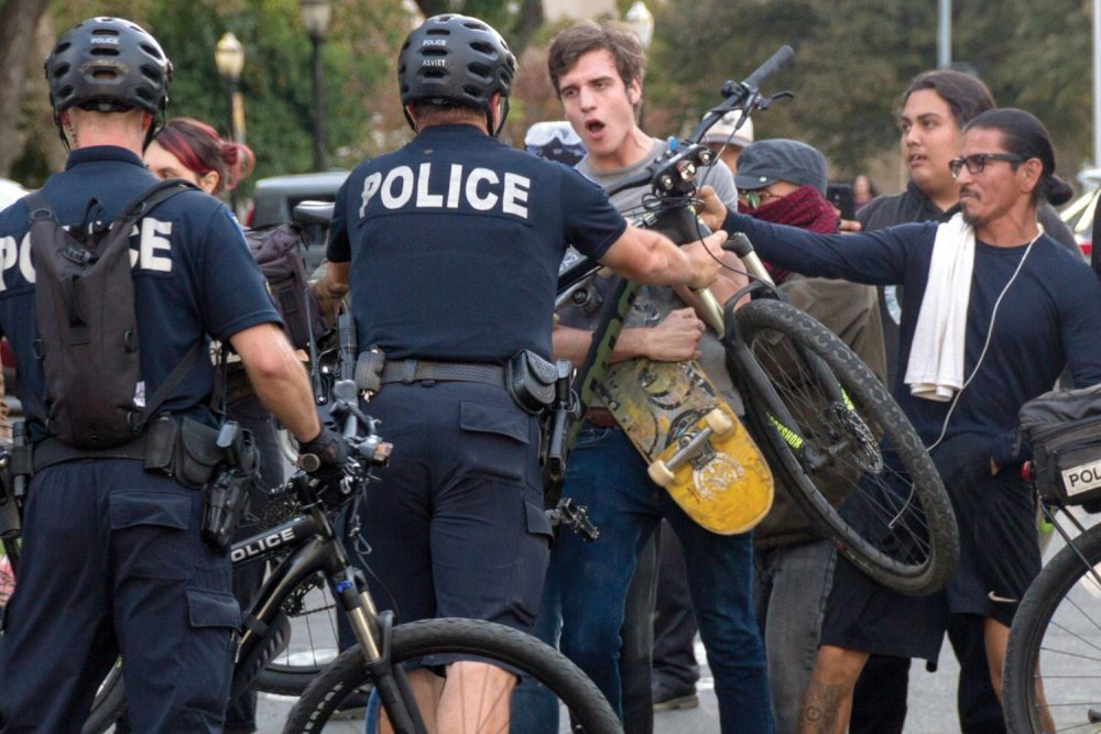 "Sacramento Police use their bikes to push counter-protestors off the street during a ""Turn California Red"" conservative rally at the California State Capital on Nov. 4, 2018. (Photo by Patrick Hyun Wilson)"