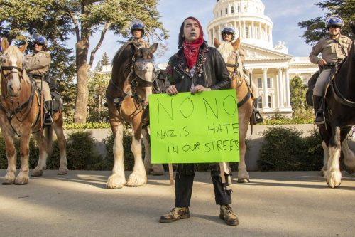 "Counter protester Jules Miller holds up a sign that reads ""No Nazi No Hate in Our Streets"" during a  ""Turn California Red"" conservative rally at the California State Capitol in Sacramento on Nov. 4, 2018. (Photo by Ashley Hayes-Stone)"