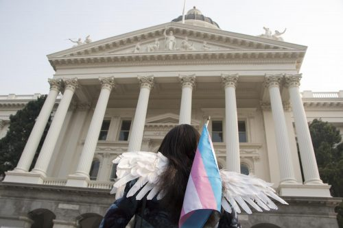 A protester carries a transgender pride flag and wears angel wings during the #StillHere Capitol March & Rally for Trans Justice at the California State Capitol in Sacramento, Calif. on Nov. 10, 2018. The wings symbolize the many transgender women who have been murdered. (Photo by Ashley Hayes-Stone)