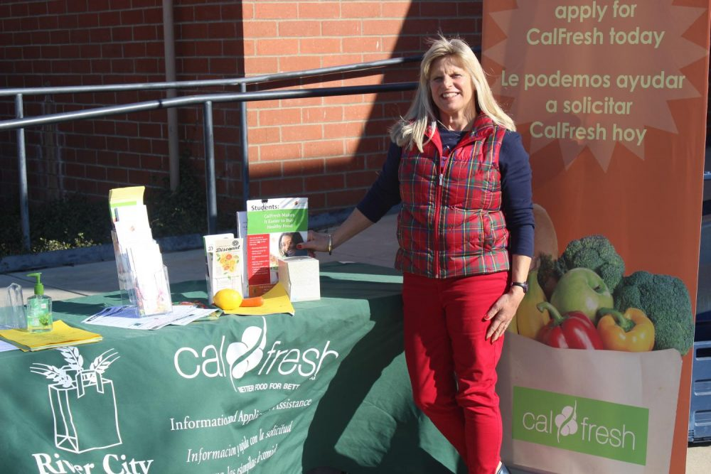 Amy Dierlam, CalFresh Outreach Director with the River City Food Bank, in front of the Kinesiology Department helping students apply for CalFresh and giving those who have CalFresh fruits and vegetables.(Photo by Breawna Maynard)