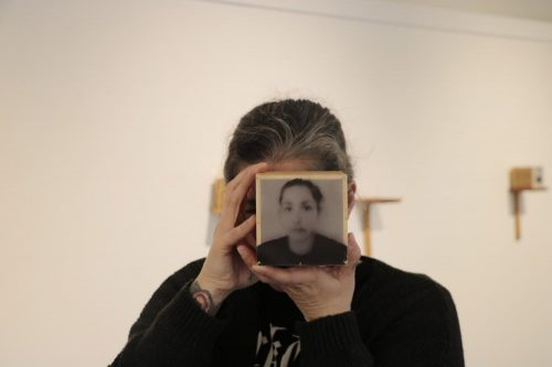 "Photographer Angela Casagrande displays her exhibition, ""Everything will Disappear,"" at the James Kaneko Gallery at American River College on Nov. 28, 2018. Casagrande holds up a box with a picture of her on it. The box contains pieces of her hair because she said making these boxes caused her a lot of stress and made her lose hair. ""Everything will Disappear"" will run at the Kaneko Gallery until Dec. 14. (Photo by Gabe Carlos)"