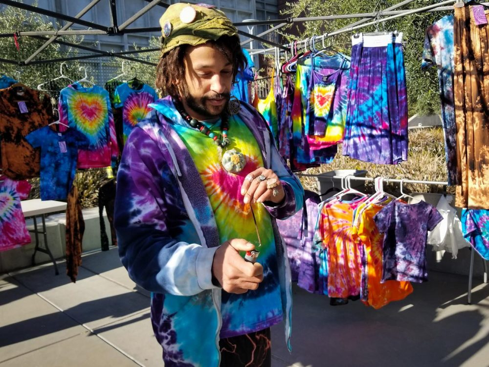 "Darryl Glass, an artist and vendor, lights incense in front of his friends' booth at the last day of the Winter Fair Gift Market in front of the Student Center at American River College on Dec. 6. He sells smudge bundles made of lavender, sage, mudwort, and yarrow he grows in his yard, and feathers from his hens and turkeys. ""I like to live off the land and I like to show people truly what mother nature provides us is beauty, and the healing aspect so that's why I do it,"" Glass said. ""To make people happy, to heal them, nurture them, cleanse whatever negative energies that are around them."""
