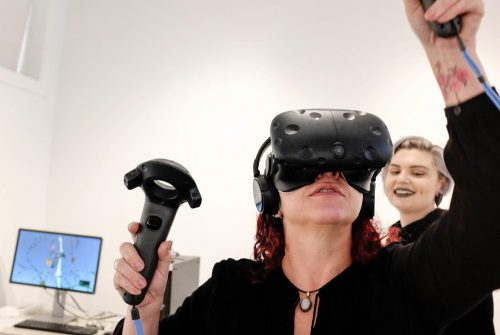 Frankie Vanity, a gallery intern, demonstrates a Virtual Reality segment of Ecotones, an interactive exhibit in the James Kaneko Gallery by artist Rachel Clarke. Gallery intern Jade Jacobs assists in the background on Jan. 28, 2019. (Photo by Patrick Hyun Wilson)
