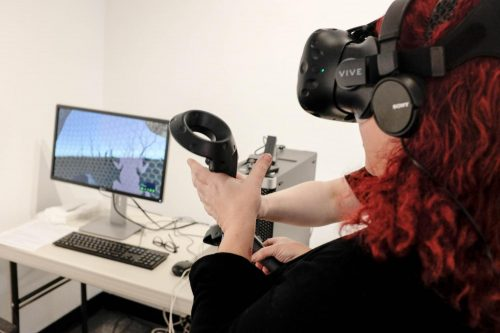James Kaneko Gallery intern Frankie Vanity demonstrates the virtual reality segment of the current exhibition Ecotones. The exhibition is an installation by Rachel Clarke, at James Kaneko Gallery from Jan. 22 until Feb. 12, 2019. (Photo by Patrick Hyun Wilson)