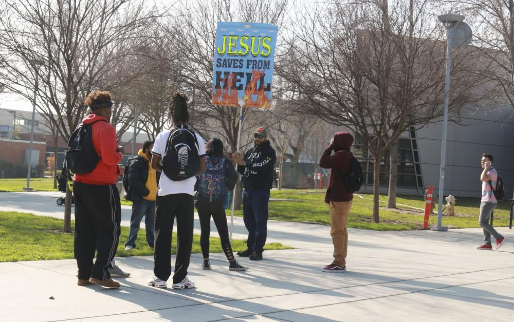 """A self declared """"Preacher of God"""" protests and holds a protest sign that reads """"Jesus Saves From Hell"""" in front of the Student Center at American River College on Jan. 30, 2019. ARC's Public Information Officer Scott Crow addressed the situation in an email."""