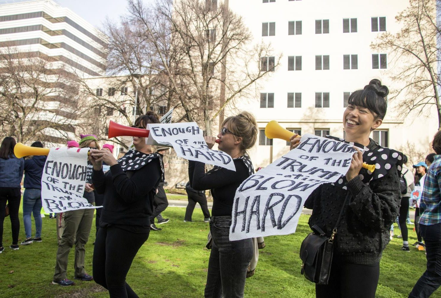 "Demonstrators hold up toy trumpets with banners that read ""Enough of the Trump-eting Blow Hard"" during the third annual Women's March in Sacramento,Calif. on Jan. 19, 2019."