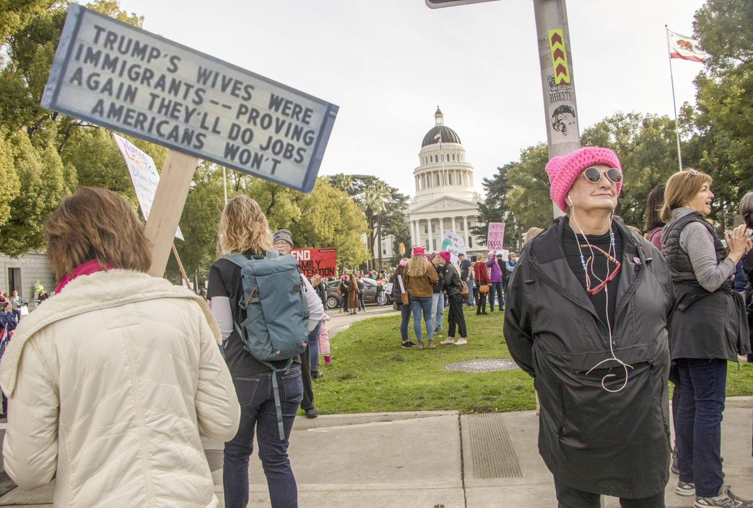 "A demonstrator holds up a sign that reads ""TRUMP'S WIVES WERE IMMIGRANTS–PROVING AGAIN THEY'LL DO JOBS AMERICANS WON'T"" as marchers make their way to the California State Capitol during the Women's March on Jan. 19, 2019."