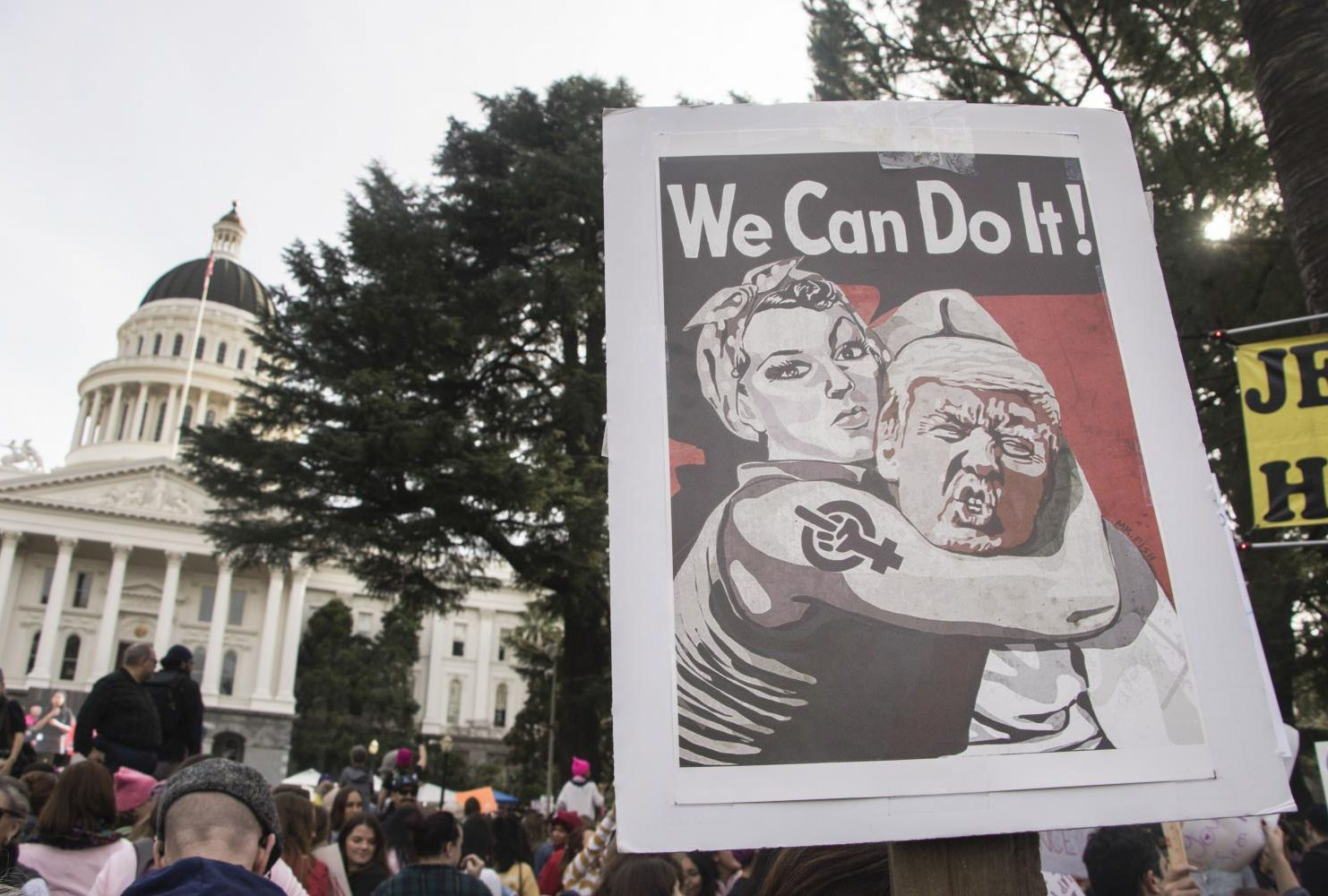 "A demonstrator holds up a protest sign that reads ""We Can Do It!"" in front of California State Capitol during the third annual Women's March in Sacramento,Calif. on Jan. 19, 2019."