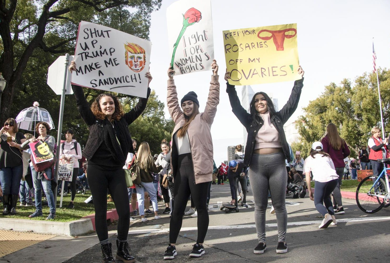 "articipants of the third annual Women's March hold up signs that reads left to right ""Shut Up Trump Make Me A Sandwich"", ""Fight For Women's Rights"" and ""Keep Rosaries Off My Ovaries"" at the California State Capitol in Sacramento, Calif. on Jan. 19, 2019."