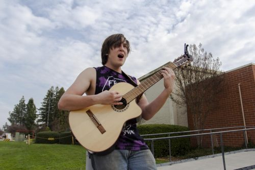 """Charlie Mullennix, music major at American River College, performs """"Welcome to Paradise"""" by Green Day in front of the Kinesiology & Athletics Building on Jan. 29, 2019. (Photo by Katia Esguerra)"""