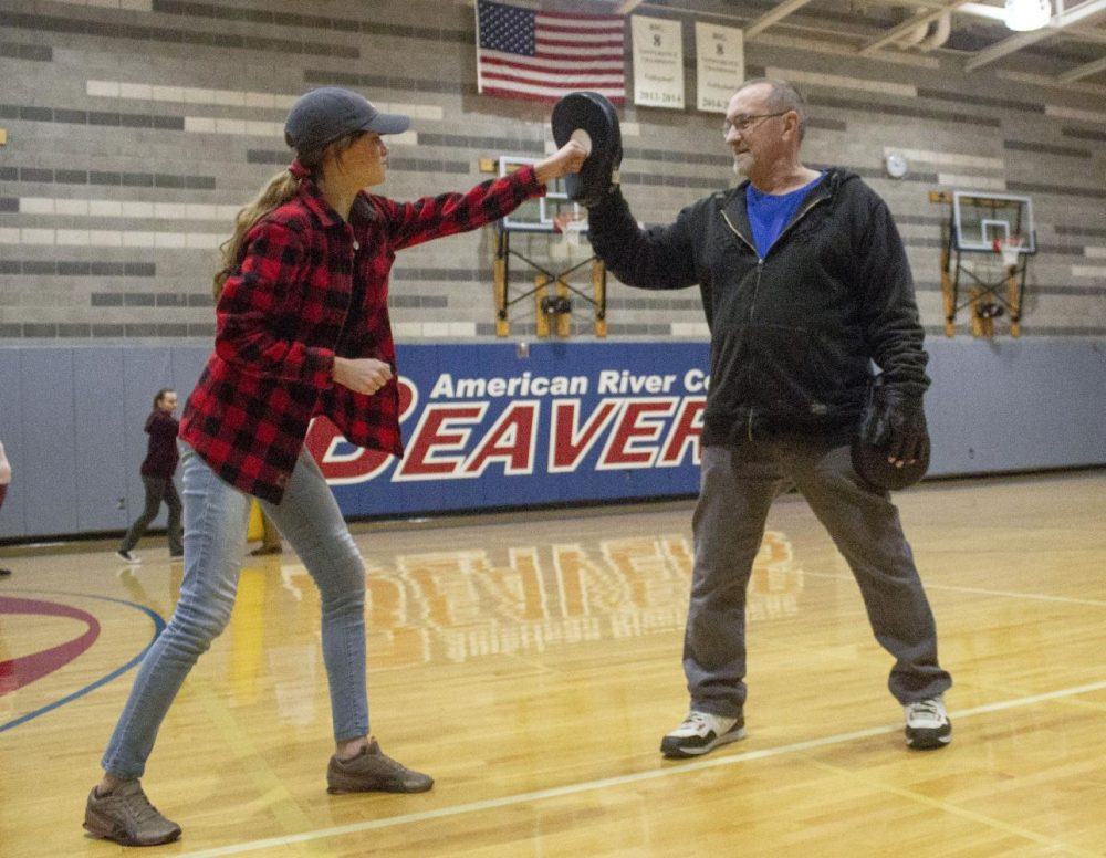 Clint LeMay, assistant to the head instructor, runs drills with mits for dental hygiene major Yelena Vovk during the Personal Safety class in the fitness department at American River College on Feb. 12, 2019. (Photo by Alexis Warren)