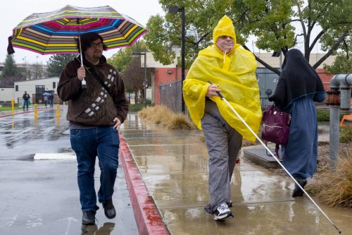 History major Jordan Alberti and human services major Paul McIntyre make their way across campus in the rain underneath an umbrella and inside a poncho on Feb. 26, 2019. (Photo by Patrick Hyun Wilson)