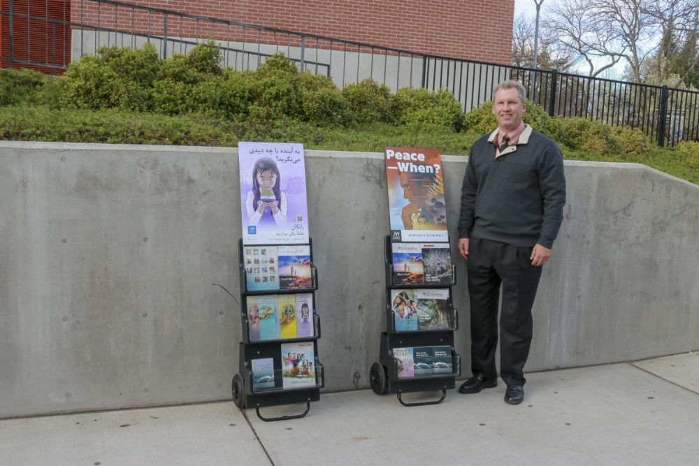 Jeff Goodone, a volunteer for the Jehovah's Witnesses organization, gives free posters, books and information about the Christian religion in multiple languages; such as Farsi, English and Russian to the students in front of Student Center at American River College on Feb. 5, 2019. (Photo by Hameed Zargry)